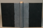 A book, with the spine covered in blue-gray leather and the boards with black Cave Paper