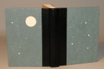 A quarter-leather book with vellum inlays of various sizes, creating a scene of a night sky.