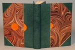 A book with green leather spine and corners, marbled paper, and parchment inlays.