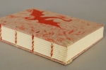 A small Coptic volume. The handmade paper on the cover has the design of a red dragon on it.