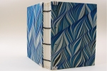 A Coptic binding covered in blue marbled paper, standing upright