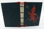 A Coptic binding covered in black handmade paper with a red dragon on the front in pulp paint.