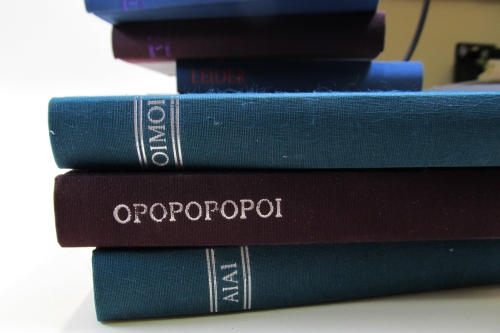 "Three case bindings lying down, titled with Ancient Greek words meaning ""Alas!"""