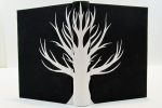 Case binding in full black cloth with a paper onlay of a white tree across the spine